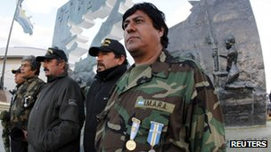 Argentine veterans of the Falklands War pose in front of the Malvinas Monument in Ushuaia, Argentina