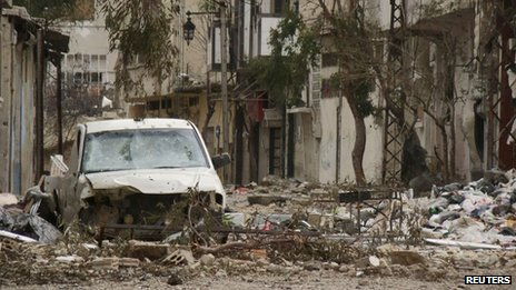 Damaged car and buildings in the Old City of Homs (30 March 2012)