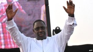Macky Sall holding his arms in the air