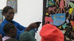 Weya artist Melania Mazinyani showing children how to embroider at Zimbabwe's National Gallery in Harare