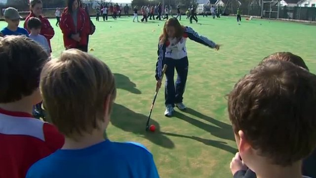 Sarah Thomas shows some hockey tips to Merthyr children