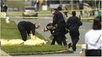 Oakland Police cover bodies near Oikos University in Oakland, California, 2 April 2012