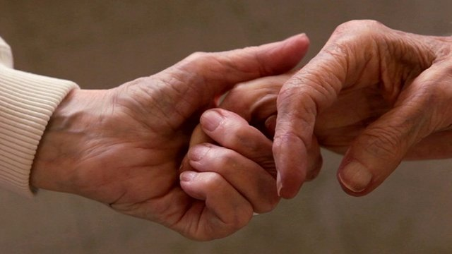 A close up of elderly women holding hands