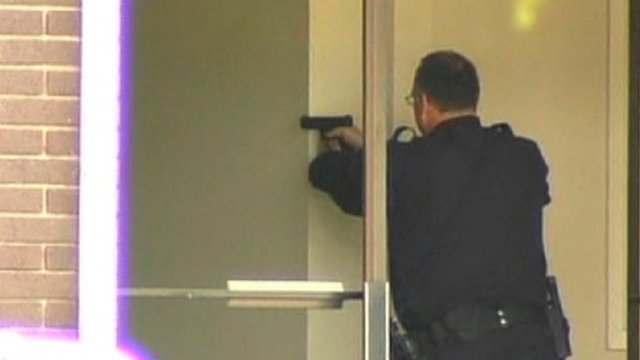 A police officer aims his handgun after a gunman entered a private Christian college in Oakland, California