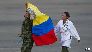 A former Farc hostage draped in a Colombian flag punches the air as he steps off the helicopter that carried him to freedom