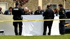 Police examine bodies outside the university