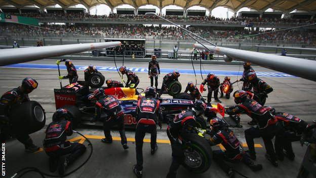 Red Bull mechanics work on Mark Webber's car during the Malaysian Grand Prix
