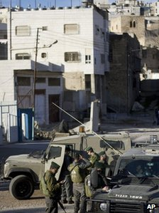 Israeli soldiers stand outside the house in the West Bank city of Hebron, which Jewish settlers have been asked to leave (3 April 2012)