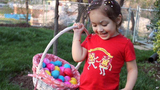 A young girl carries a pink basket filled with colourful painted eggs. She has sprinklings of pastel confetti in her hair.