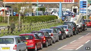 Cars queue for petrol outside a garage