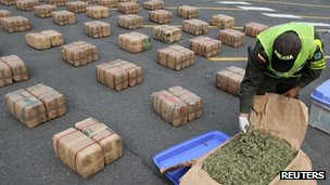 A Colombian police officer inspects a pack of confiscated marijuana in Cali February 27, 2012.