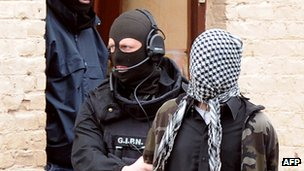 Police officer wearing a balaclava holding suspect with a scarf over his head