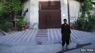 A private security guard stands outside the residence of Hafiz Saeed