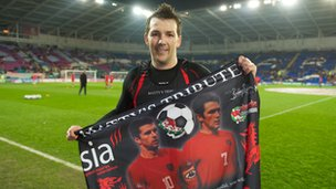Matt Jones holds up a flag paying tribute to Gary Speed prior to Wales' home friendly against Costa Rica