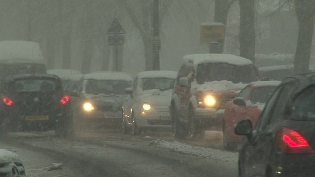 Snow covered cars stuck in traffic