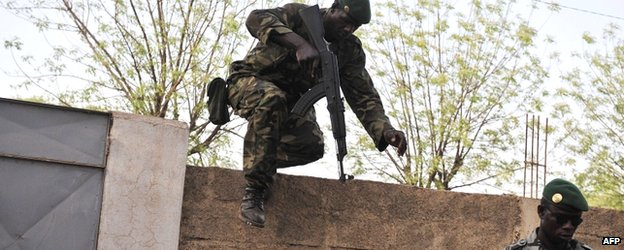 A Malian soldier leaps over a wall as another stands guard on 3 April 2012 at the Kati military camp near Bamako