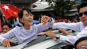 Aung San Suu Kyi waves to the crowd as she leaves her National League for Democracy headquarters in Yangon on April 2, 2012