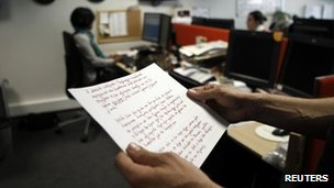A Reuters journalist in Athens, 5 April, reads a copy of the suicide note left by Dimitris Christoulas