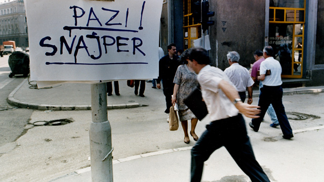 A man crossing the street in Sarajevo next to a sign warning of snipers