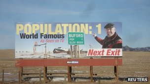 Undated picture of a billboard showing Don Sammons, owner of the smallest town in the US, one exit away from Buford, Wyoming