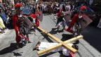 A man playing Jesus lies under a wooden cross while he is lashed by Roman soldiers, 6 April 2012
