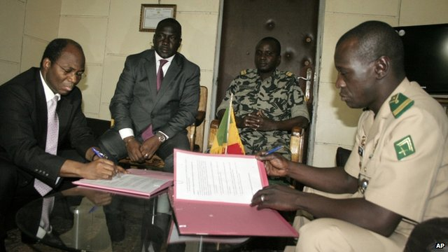 Coup leader Captain Amadou Sanogo and Burkina Faso Foreign Minister Djibrill Bassole signing deal