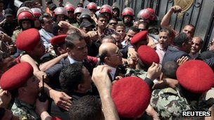 Egypt&#039;s former vice president Omar Suleiman (C), is mobbed at the Elections Commission (HPEC) headquarters in Cairo, 8 April 2012