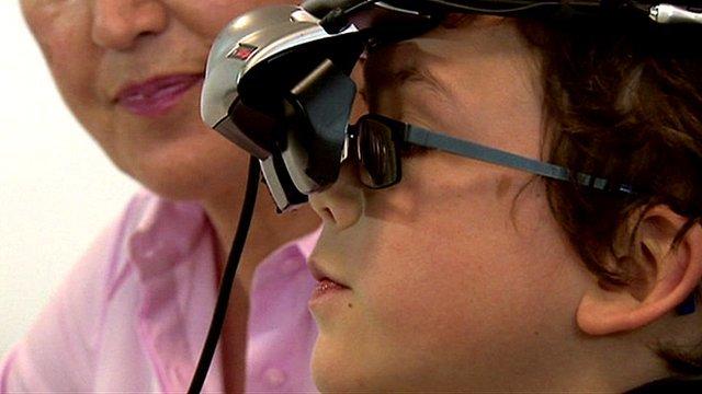 boy takes eye test wearing special glasses