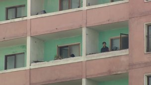 Woman on a balcony of tower block, 9 April 2012