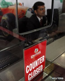 A Kingfisher Airlines employee sits behind a closed counter in Mumbai (March 2012)