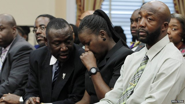 Sybrina Fulton, mother of Trayvon Martin, listens to her lawyer Benjamin Crump (l) as Trayvon's father Tracy looks on.