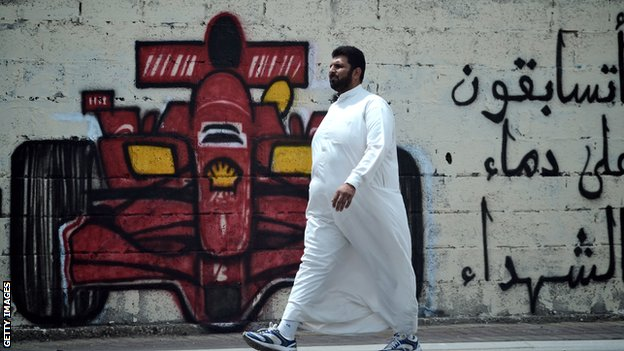 A man walks past anti-Bahrain GP graffiti 