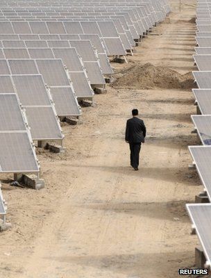Man walking through a solar power array (Image: Reuters)