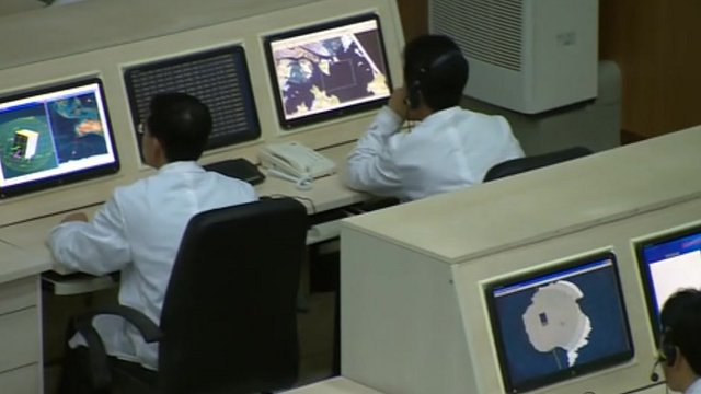 Men looking at computers inside North Korea&#039;s mission control
