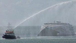 Condor being given a celebratory water salute by the States tug