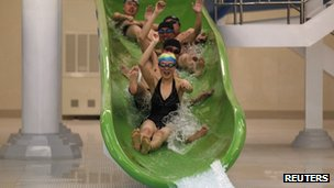 North Korean students ride down a water slide into a swimming pool at Kim Il-sung University in Pyongyang (April 11, 2012)