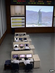 North Korean technicians watch live images of the rocket Unah-3 at the satellite control room of the space centre on the outskirts of Pyongyang (April 11, 2012)