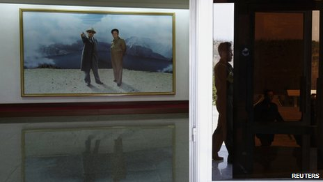 A North Korean visitor is reflected on a glass door to the lobby of the satellite control centre of the Korea Committee of Space Technology