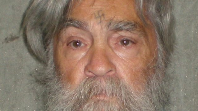 Close up of Charles Manson's face as an older man - with swastika he engraved on his forehead visible.