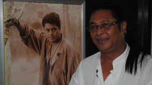 Actor and director Kyaw Thu in front of a picture of himself during his acting heyday.