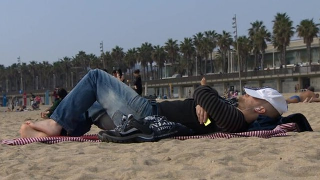 Man lies on beach in Barcelona