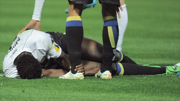 Kenya and Parma's McDonald Mariga lying injured on the pitch