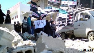 Demonstrators with the Syrian opposition flags protest against Syria's President Bashar Al-Assad after Friday prayers in Al Qasseer city, near Homs April 13, 2012