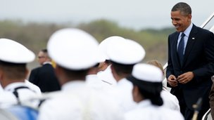 US President Barack Obama walks through an honor cordon upon arrival on Air Force One at Rafael Nunez International Airport in Cartagena, Colombia on April 13, 2012