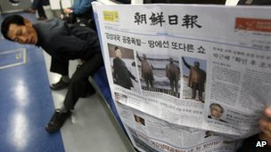 "A subway passenger reads a South Korean newspaper Chosun Ilbo reporting North Korea""s rocket launch"
