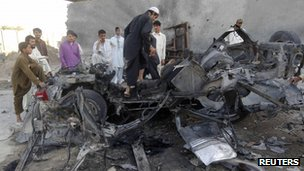 Afghan men stand around the wreckage of a car used by a suicide attacker in Jalalabad province (April 15, 2012)