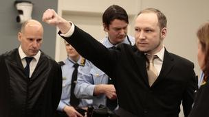 Anders Breivik gives a closed-fist salute while entering the courtroom in Oslo (16 April 2012)