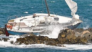 Yacht stuck on rocks outside St Peter Port Harbour