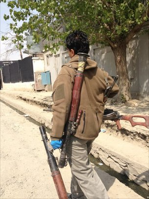 An Afghan soldier carrying weapons left behind by insurgents
