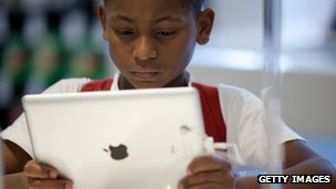 A young boy looks at an Apple iPad